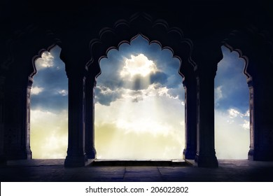 Indian arch silhouette in old temple at dramatic sunset sky with light hole in the clouds