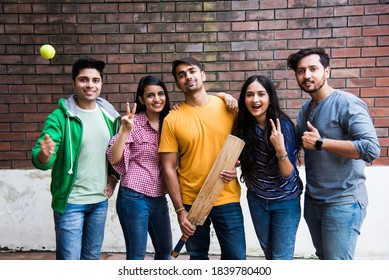 Indian asian college students or friends playing cricket match as outdoor sport activity