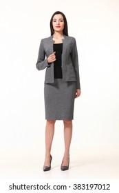 indiase aziatische oosterse brunette business executive vrouw met rechte kapsel in twee stukken jas en rok pak hoge hakken schoenen volledige lengte lichaam portret staan geïsoleerd op wit