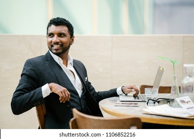 An Indian Asian man in a 3-piece suit is sitting at a table and is looking up from his work on his laptop and smiling openly.