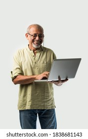 Indian asian senior adult man or grandpa using laptop and holding paper currency notes against white background