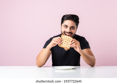 Indian Asian young bearded man eats bread sandwich while sitting in kitchen or dining table. Showing or presenting
