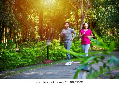 Indian asian young Couple jogging, running, exercising or stretching outdoors in park or nature