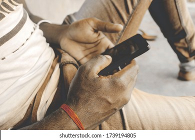 An Indian or asian young man having addicted or fun together using phones. Detail of hands sharing content on social network with mobile phones. Hand body part visibleAIR DISEASE CRISIS TEENS TEENAGER