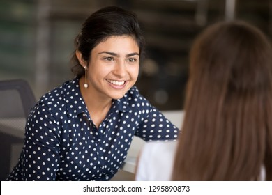 Indian attractive positive woman talking with colleague sitting at desk in office room, focus on hindu female. Diverse millennial smiling employees have break communicating together at coworking area