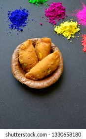 Indian authentic dessert or sweet - Gujeeya, served in an eco- friendly leaf bowl. Holi festival special sweet with assorted powder colors.
