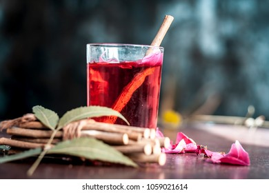 Indian Ayurvedic and Islamic way of cleaning teeth and brushing it with using miswak or Neem bark with rose water on wooden surface in dark Gothic colors.