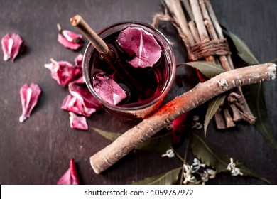 Indian Ayurvedic and Islamic way of doing brush with using miswak or Neem bark with rose water on wooden surface in dark Gothic colors.