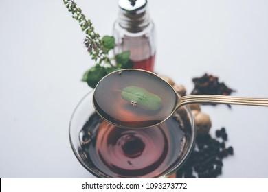 Indian Ayurvedic Kadha/Karha or health tonic for fighting seasonal infections, made using ginger, tulsi, black pepper, clove and honey. Selective focus