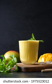 Indian ayurvedic mango lassie or lassi on black background. Vertical format. Traditional healthy drink with mango. Freshness lassi made of yogurt, water, spices, fruits and ice.