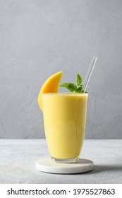 Indian ayurvedic mango lassie or lassi on light gray background. Vertical format. Traditional healthy drink with mango. Freshness lassi made of yogurt, water, spices, fruits and ice.