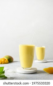 Indian ayurvedic mango lassie or lassi on light gray background. Vertical format. Mango lassie traditional healthy beverage with yogurt, water, spices, fruits and ice.