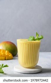 Indian ayurvedic mango lassie or smoothie on light gray background. Close up. Traditional healthy vegan beverage with mango. Freshness lassi made of yogurt, water, spices, fruits and ice.
