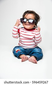 indian baby boy or infant trying to wear dark glasses or sunglasses or goggle, isolated over white background