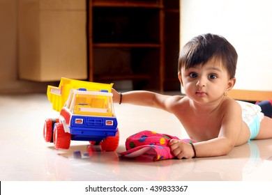 indian baby on ground with small truck toy