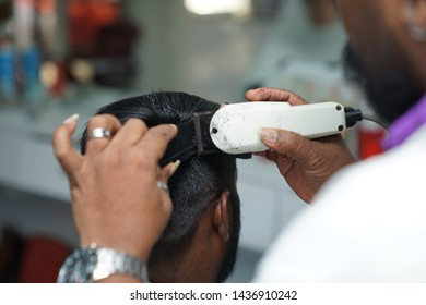 An Indian barber cutting hair of male client using machine hair clippers. Hairstylist serving customer at the barbershop.