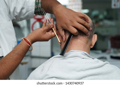 An Indian barber shaving a client's beard in a barber shop.