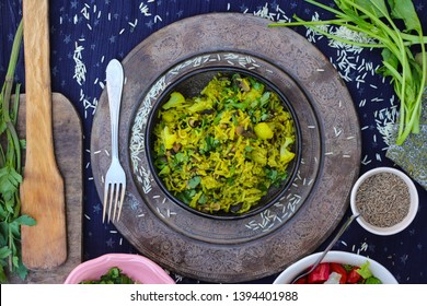 Indian basmati rice pilau (pilaf) with cilantro, spinach, spices, herbs in bowl with fried, cooked vegetables. Vegan lunch, vegetarian dinner, healthy food