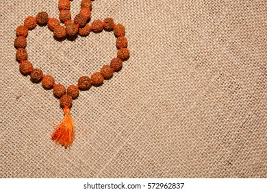 Indian beads of Rudraksha are on the background burlap.