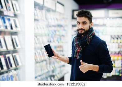 Indian beard man customer buyer at mobile phone store choose his new smartphone and show thumb up. South asian peoples and technologies concept. Cellphone shop.