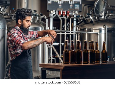 Indian bearded tattooed hipster male manufacturer presenting craft beer in the microbrewery.