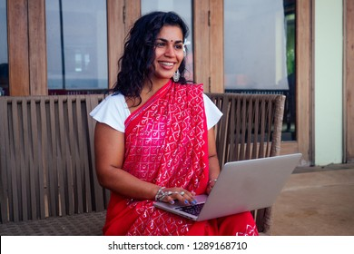 indian beautiful businesswoman working on a modern laptop in the cafe restaurant on the shore of the paradise ocean.Web Designer girl freelancer in india in the sea .remote work ,concept copywriter