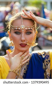 indian beautiful Caucasian woman in traditional blue dress.hindu model with golden kundan jewelry set bindi and nose ring piercing nath fashion photoshoot on the street among motorcycles and market