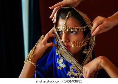 indian beautiful female in golden rich jewelery and tradition saree face closeup professional make-up wearing bindi on head .Artist doing to muslimgirl with bindis maang tikka ,nath,nose Pin