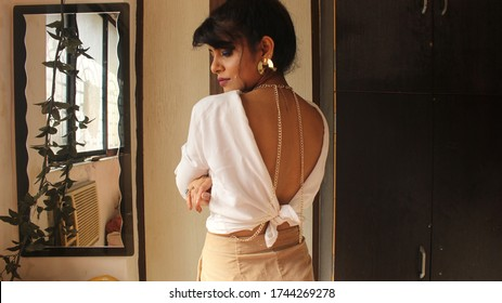 An Indian Beautiful Girl in Backless Shirt with Jewellery Posing In Home and Against White with Mirror infront of Window thinking