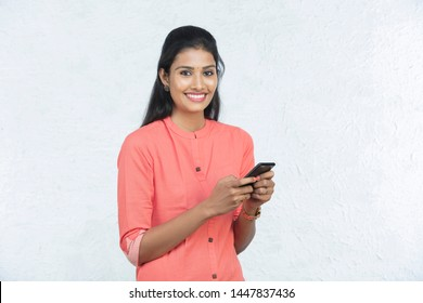 indian beautiful woman holding phone and talking in white background