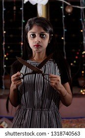 An Indian beautiful woman with a psycho look and big scissor in the hand is standing vaguely inside a room full of light bokeh. Indian Halloween