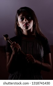 An Indian beautiful woman with a psycho look and hammer in the hand is standing vaguely inside a room with white background. Indian lifestyle and Diwali celebration