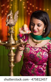 Indian Beautiful young girl in traditional wear lighting oil lamp or samai with diya and celebrating ganesh festival or Diwali