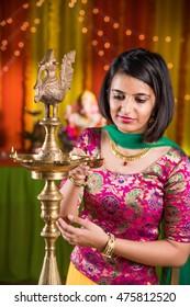 Indian Beautiful young girl in traditional wear lighting Diya Or Samai Lamp on ganesh festival or Diwali