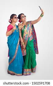 Indian Beautiful young girls in traditional wear, Nauvari saree & sunglasses. Taking selfie pictures on white background.