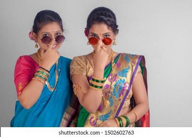 Indian Beautiful young girls in traditional wear saree, Nauvari & sunglasses.