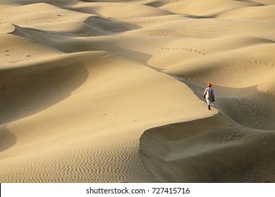 Indian bedouin is going all over the peak of the sand dune on the Thar desert, Rajasthan, India