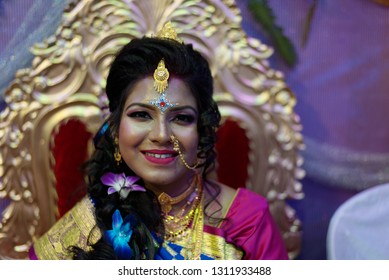 Indian Bengali bride in bridal dress and make up is sitting on a decorated chair on wedding day. Indian wedding, culture and lifestyle