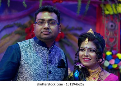 Indian Bengali bride and groom in traditional wedding dress and make up are standing in front of a floral background on the wedding day. Indian wedding, culture and lifestyle
