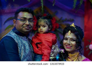 Indian Bengali bride and groom in traditional wedding dress and make up are standing in front of a floral background on the wedding day with a baby infant girl. Indian wedding, culture and lifestyle
