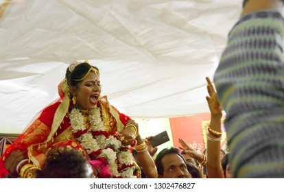 Indian Bengali bride shouting out of fear when she was held up in air on wedding day. Indian wedding and rituals