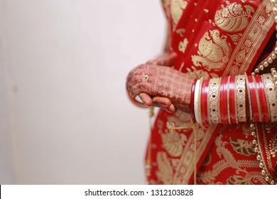 Indian Bengali Punjabi bride in Banarasi saree holding hands showing her choora and sakha polla bangles against an off-white background.