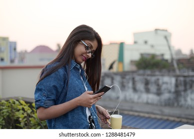 Indian Bengali woman in blue casual jacket is listening to music or talking to someone on rooftop with earphone plugged in her ear and sipping from a coffee mug in her hand. Indian lifestyle