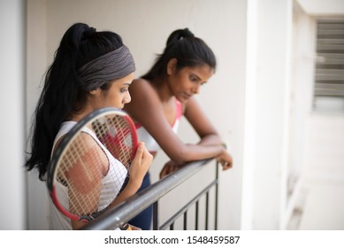 Indian black and white brunettes girls with a tennis bat enjoying themselves in sportswear on a balcony in a white background. Indian lifestyle