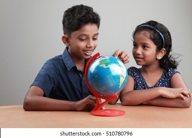 Indian boy and girl look at the globe on a study table