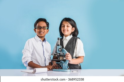indian boy and girl withmicroscope, asian kids with microscope, Cute little kids holding microscope, 10 year old indian boy and girl and science experiment, school students doing science experiments