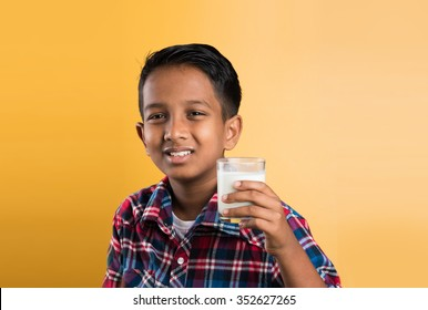 indian boy with a glass of milk, closeup portrait on yellow background
