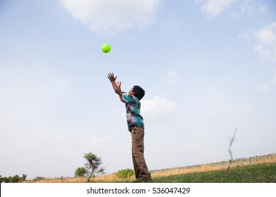 Indian boy playing  with ball on the field - in action.