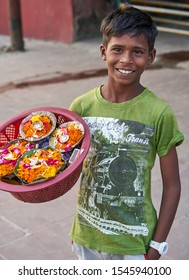 Indian boy sells flowers on the waterfront in Rishikesh, Rishikesh, India. 27.10.2019