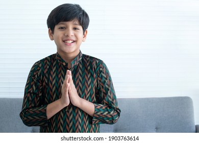 Indian boy in traditional clothes holding palms together over chest in Namaste gesture, smile and lookin at camera, welcome expression of invitation or greeting Namaste